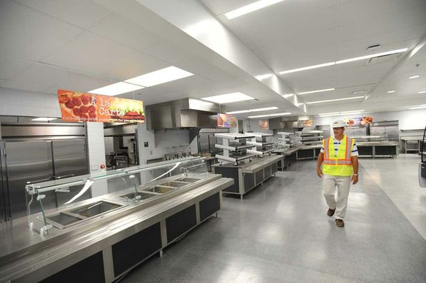 Photo by Andy Shupe—                                                                                        Officials walk through the cafeteria Thursday, Aug. 3, 2012, during a tour of the additions to the Fayetteville High School building.