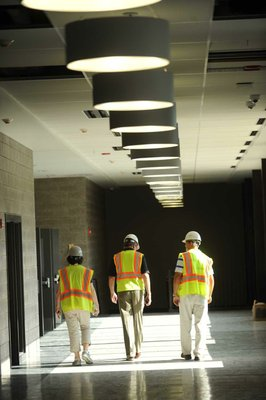 Photo by Andy Shupe—                                                                                        Officials walk through the hallways Thursday, Aug. 3, 2012, during a tour of the additions to the Fayetteville High School building.