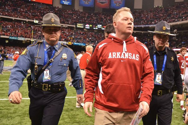 Former University of Arkansas Coach Bobby Petrino leaves the field escorted by Capt. Lance King of the Arkansas State Police after the 2011 Allstate Sugar Bowl in New Orleans. The state police agency is setting a strict policy for troopers who provide security at athletic events.