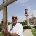 Mike Fisher of McDonald County, Mo., holds a cross in support of Chick-fil-A as cars back up at the ...
