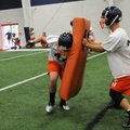 Wilder Blockburger, left, slams into pads held by Utah Julius while running through drills Friday in...