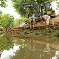 Johnny Kinard, center, and Joshua McDonald, right, workers with Southern Excavation in Fairhope, Ala...
