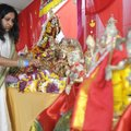 Lisa Das of Rogers places fresh flowers around deities at the new Hindu Association of Northwest Ark...