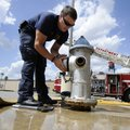 Rob Sampier, a Rogers firefighter and paramedic, caps a fire hydrant July 25 in front of Fire Statio...