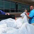 Hunter Rogers, right, with the Jones Center, loads bags Thursday filled with backpacks and school su...