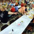 Kristie Hendricks motions Thursday to empty spots for people at the annual Tontitown Grape Festival'...