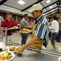 Randy Pianalto hands out plates Thursday during the spaghetti dinner at St. Joseph Catholic Church's...