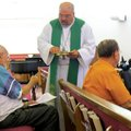 The Rev. Paul Hass serves communion Aug. 7 during the First Tuesday communion service at Bella Vista...