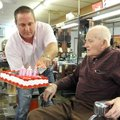 Scott Greenwood, left, lights candles on a cake Friday for H.K. Bonds for his 100th birthday at the ...