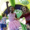 Cheney Wilson, 8, from left, Eva Byars, 5, and Ana Hays, 6, jump around in an inflatable bounce hous...