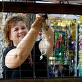 Jo Fantinel of Clifty hangs jewelry Friday at her booth during the Arts & Crafts Fair at the 114th T...