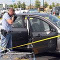 Michael Hendrix, a Springdale police detective, examines a Ford Focus on Aug. 3 in the Walmart parki...