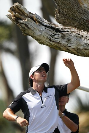 Rory McIlroy reaches for his ball after it became stuck in a tree on the third hole during Saturday's round at the PGA Championship. McIlroy took a drop and a penalty but made par on the hole.