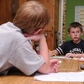Lucas Burchar, 9, left, listens as Cameron Green, 9, explains to classmates how he solved a fraction...