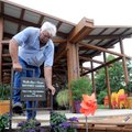 Gerald Klingaman, operations director, puts a new sign in front of the butterfly garden Aug. 3 at th...