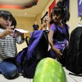 Elizabeth Cubrero, 5, left, and sister Marissa Cubrero, 7, check out the basic school supplies in th...