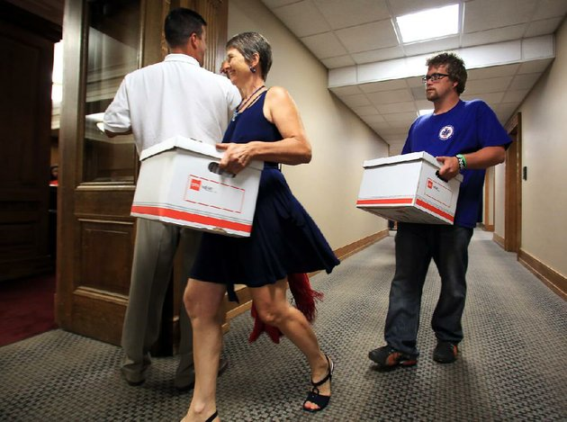 emily-williams-and-brian-hill-help-deliver-boxes-of-signatures-to-the-secretary-of-states-office-monday-aug-13-arkansans-for-compassionate-care-collected-74406-signatures-to-try-to-ensure-the-2012-arkansas-medical-marijuana-act-is-on-the-november-ballot