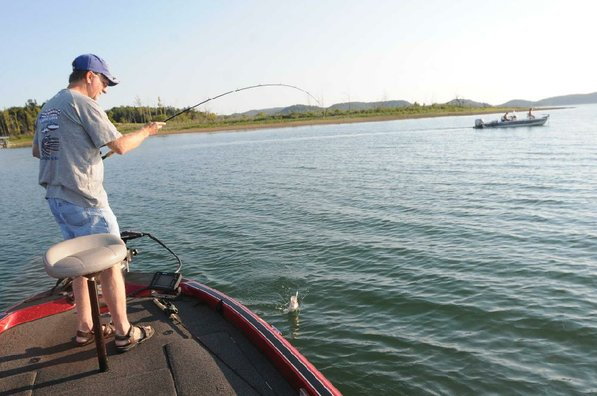 Brashers lands a white bass while other anglers troll nearby.