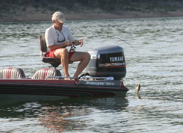 Grimsley Graham catches a white bass while fishing with his friend Bob Ross near Brashers' boat.
