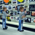 Nicholas Graziani, left, and his twin Zachary, age 4 from Bentonville, take a look Friday at the pho...
