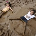 Sofia Simon, 6, right, and Audrey Pender, 5, both of Rogers, make angels in a mud puddle Friday on o...