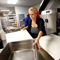 Theresa Warford sends cutting boards and containers through the washer Thursday inside the new cafet...