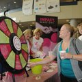 Becky Payne, a teacher at Westside Elementary School, spins a wheel to win a prize at the Susan B. K...