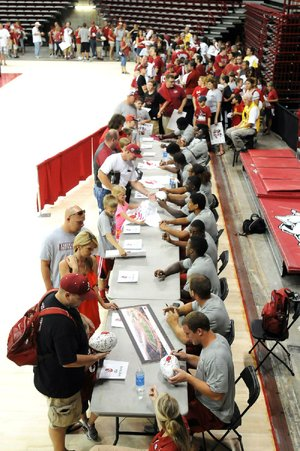 Thousands of fans lined up to get autographs from the Arkansas football team, including the linebackers seen here, during Saturday's fan day at Walton Arena in Fayetteville. Arkansas officials estimated the crowd at Saturday's scrimmage at 15,000.