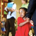 Tavian Daniels, 4, holds tightly on to his father, Todd Daniels, both of Rogers, Monday inside Shilo...