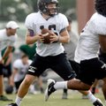 Reece Dollins, Bentonville High School quarterback, drops back to pass on Aug. 8 during practice ins...