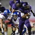 Braydon Cook, a Fayetteville running back, breaks through Memphis University School's line on his wa...