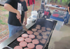 Dennis Huston takes pride in manning the large grill cooking Blackhawk Burgers under the covered pavilion the Pea Ridge Booster Club uses.