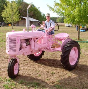 Glenn Smith, of Gentry, moves the Tired Iron of the Ozarks' breast cancer awareness tractor to display it at the club's weekend show. The tractor was also outfitted by Tired Iron members with a second seat and set of controls to teach youth how to drive a tractor. Through donations and signatures added to the tractor, more than $1,000 has been raised to assist in the fight against breast cancer.