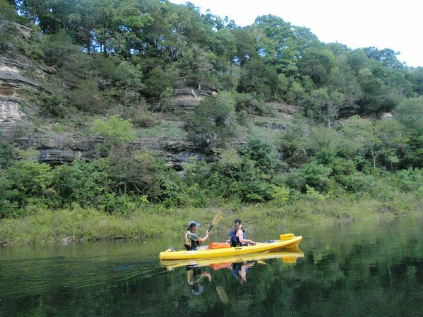 Jen Hazelrigs, the center's director, left, and Kyrie Leaf paddle past bluffs on the White River below Beaver Dam.