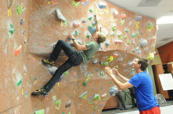 Connor Wilson tests his climbing skills on a bouldering wall while Jacob Martin spots for him on Tuesday at the University of Arkansas Outdoor Connection Center.