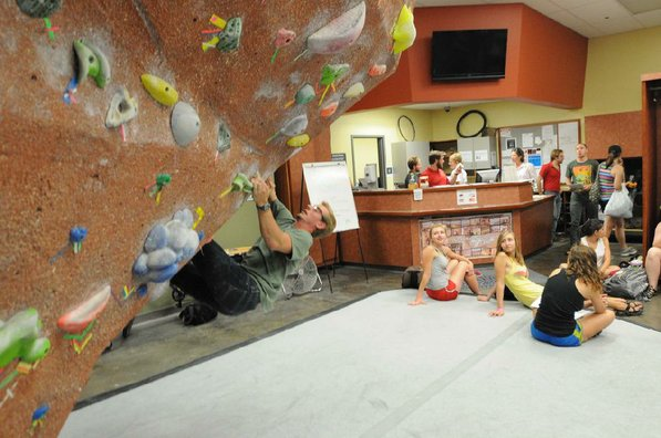 Students waiting to depart on a kayak trip watch Connor Wilson test his skills on the bouldering wall.