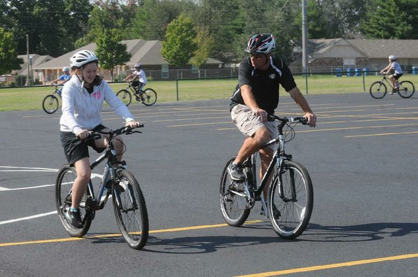 Lincoln Junior High teacher Josh Schluterman helps a student with her bike skills.