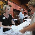 Megan Cuddy, left, with the Rogers-Lowell Area Chamber of Commerce, helps Roberta Moore of Springdal...