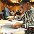 Ron Rye of Rogers tends to paperwork Friday at the Northwest Arkansas Job Fair at the John Q. Hammon...
