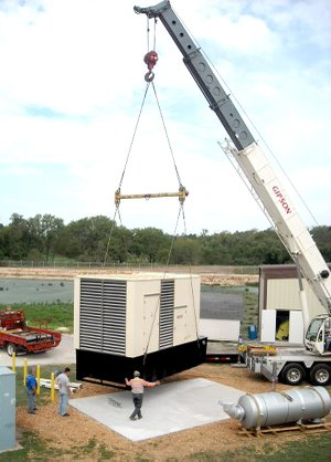 A new one megawatt diesel generator was lifted into place by cranes at Decatur's wastewater treatment plant on Thursday. The large tank in the foreground of the picture is the generator's muffler.