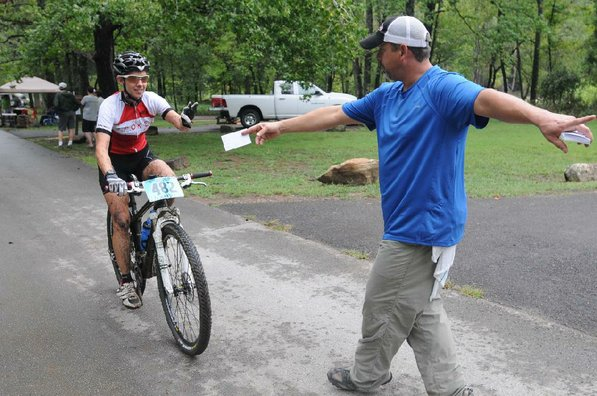 Phil Penny, right, with the Ozark Off Road Cyclists checks in a racer at the finish line.