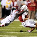 Arkansas quarterback Tyler Wilson (right) is brought down by Rutgers linebacker Khaseem Greene in th...