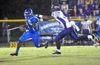 Junction City's #40 Jamario Bell catches Strong's #4 quarterback Jacoby Heard for a big loss in a shirt tail tackle during the first quarter of the game Sept. 21th.