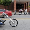 A motorcycle passes by a line of parked cruisers on Dickson Street on Sept. 13. Thousands of riders ...