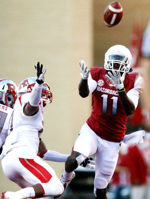 Arkansas wide receiver Cobi Hamilton (11) makes a catch in front of Rutgers defensive back Wayne Warren on Saturday. Hamilton finished with 10 catches for 303 yards and 3 touchdowns.