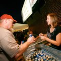 Tamra Kesner, right, of Springdale, serves a beer to Mark Nicholson of Cabot on Thursday at The Rogu...