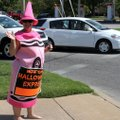 Cheryl Rust, a sign dancer for Halloween Express, waves last week to motorists at the intersection o...