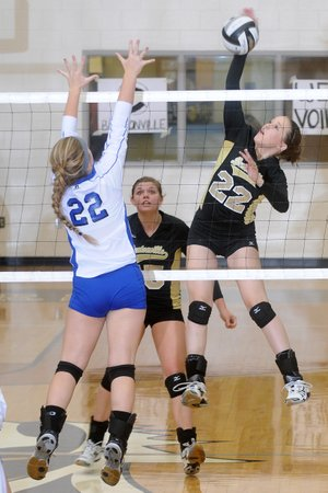 MacKenzie Muirhead, left, of Rogers High tries to block a kill by Bentonville's Anna LeDuc on Tuesday in Tiger Arena at Bentonville