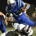 STAFF PHOTO MARC F. HENNING -- Rogers quarterback Nick Wary leaps over a Springdale defender on a ca...