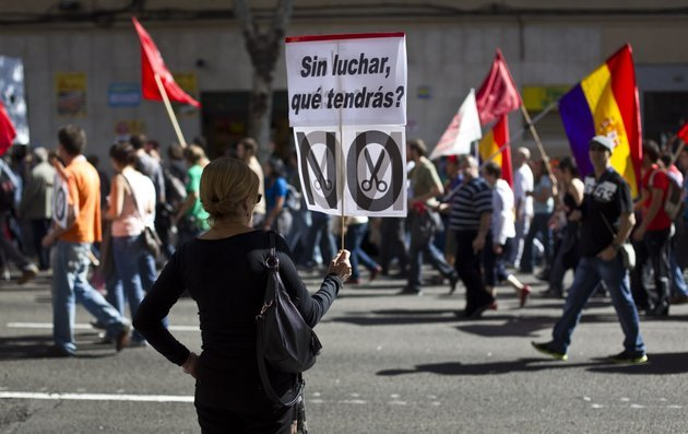 a-woman-holds-a-banner-reading-without-fighting-what-would-you-get-during-a-demonstration-in-madrid-spain-sunday-oct-7-2012-thousands-of-people-called-by-150-organizations-are-marching-in-56-spanish-cities-to-protest-punishing-austerity-cuts-they-say-will-only-increase-unemployment-and-job-insecurity